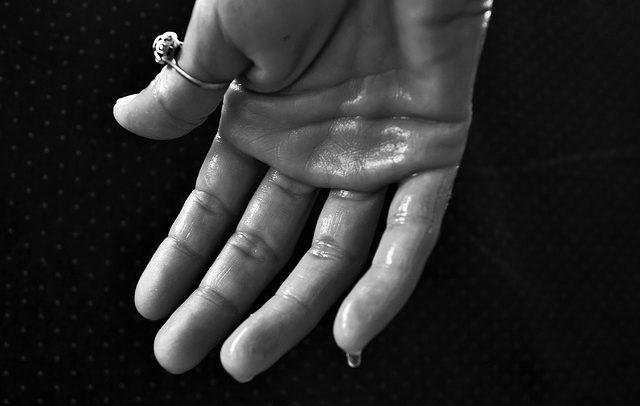 Schweißtriefende Hand